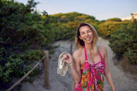 Laughing happy vivacious woman on summer vacation holding her shoes in her hand as she walks on the beach sand along a pathway through bush