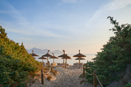 Tropical sunset or sunrise on a resort beach lighting up the sky over a calm ocean with a view down a path of umbrellas and recliner chairs on the sand