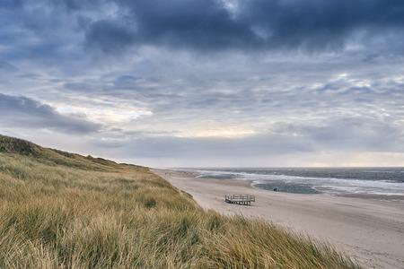 Klein platform op een verlaten zandstrand met kustgrassen die op duinen groeien onder een bewolkte stormachtige hemel en witte branding in de oceaan