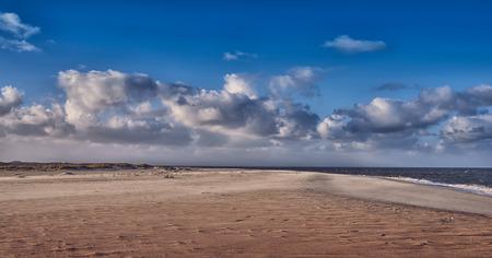 人けのない砂浜、穏やかな波が曇りの青い空の下の海岸線に沿ってのどかな夏の休暇や休暇のため