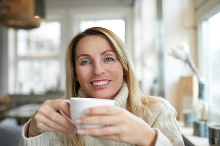 Portrait of a beautiful woman with long blond hair smiling and looking at camera while relaxing at home with a cup of coffee Stock Photo