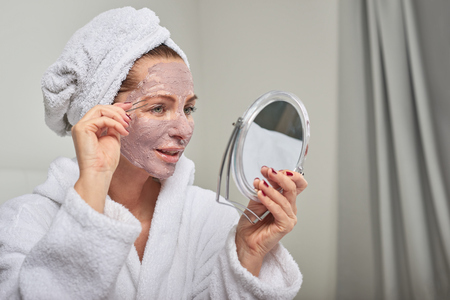 Attractive woman wearing a face mask beauty treatment holding a mirror as she plucks her eyebrows with tweezers Reklamní fotografie