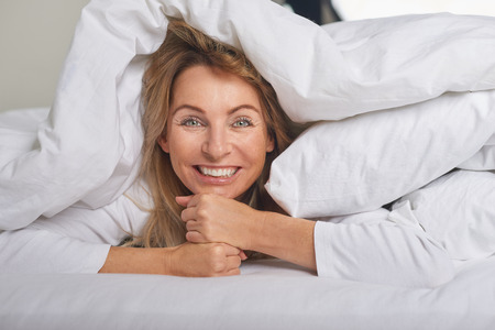 Beautiful middle-aged woman under white sheets looking at camera with a happy smile