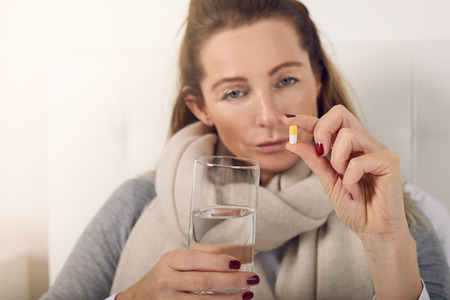 Portrait of a sick woman in bed looking at camera upset while holding a glass of water and a pill against flu symptoms