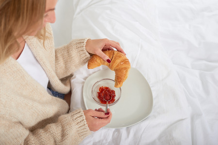 High-angle view of a young woman eating French croissant with fresh fruit jam while having a delicious breakfast in bed during weekend