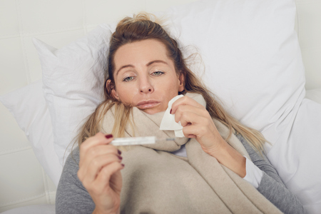 Sick woman with a miserable expression taking her temperature as she lies in bed suffering from a seasonal cold and flu trying to keep warm Stock Photo