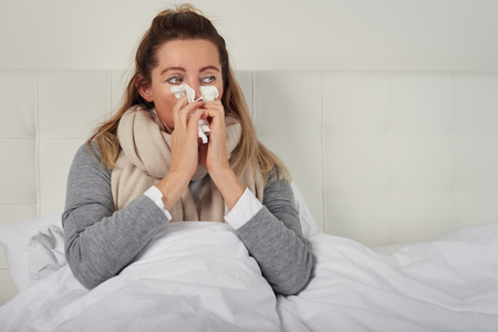 Sick woman with seasonal cold and flu lying wrapped up warmly in bed with a miserable expression blowing her nose on a tissue Banco de Imagens