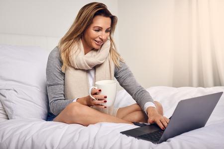 Attraktive Frau , die auf ihrem Bett eingewickelt in einem warmen gestrickten Schal mit Kaffee und einem offenen Laptop-Computer , das in die Kamera schaut