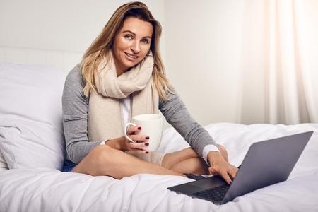 Frau arbeitet mit Laptop im Bett