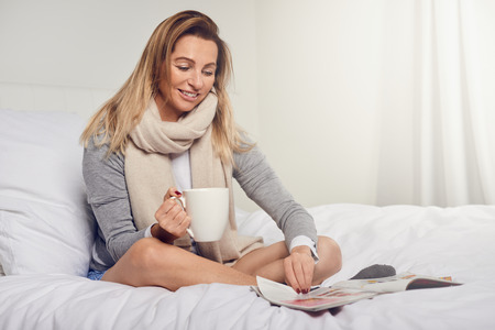 Attractive smiling contented young woman reading a magazine as she relaxes barefoot on her bed with a mug of coffee and a scarf around her neck