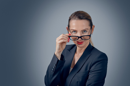 Stylish business executive peering over her glasses at the camera with a thoughtful serious expression on a grey graduated background