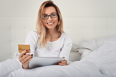 Attractive woman relaxing in bed doing online shopping holding her credit card in one hand and digital tablet in the other as she smiles at the camera Stock Photo