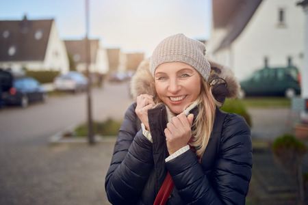 Smiling happy middle-aged woman standing outdoors on a cold winter day in a warm jacket and knitted cap in a suburban street Stock Photo