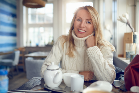 Portrait of a beautiful woman with blond long hair and blue eyes looking at camera relaxed indoors Stock Photo