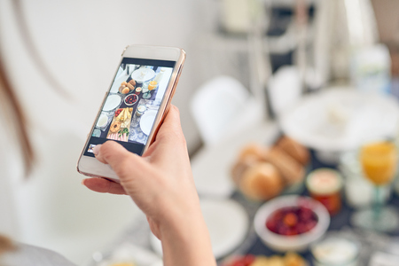 Woman taking a picture of her breakfast laid out on the table in front of her with a mobile phone and her friend looking interested at the scene