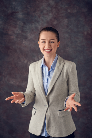 Young attractive smiling professional woman in a jacket gesturing with her hands as she explains something over a textured grey studio background Stock fotó