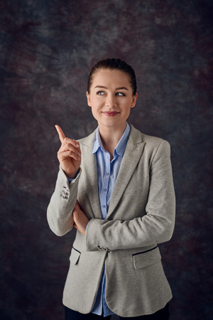 Smart smiling young professional or business woman pointing her finger in the air with a pleased smile as she finds a solution to a problem or thinks of a bright idea over a grey mottled background
