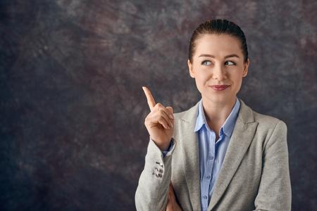 スマートな笑顔の若い専門家やビジネスの女性は、彼女が問題の解決策を見つけたり、灰色のまだら背景の上に明るいアイデアを考え、喜んだ笑顔 写真素材