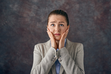 Dismayed upset young woman with her hands to her cheeks staring wide eyed at the camera with a tearful expression over a textured slate background Stock Photo
