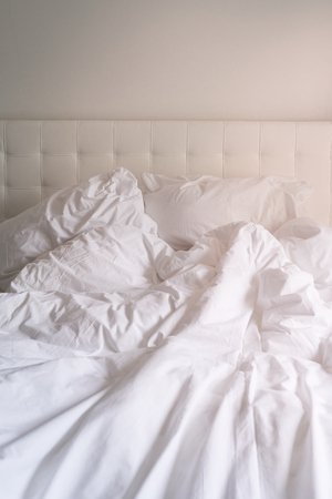Unmade bed with plain white bed linen in a close up view of a rumpled duvet, pillows and a padded headboard