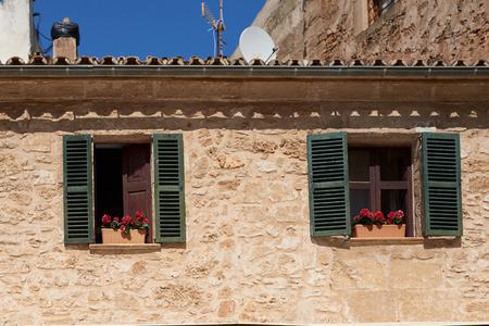 푸른 하늘에 복사 공간이 녹색 셔터와 함께 오래 된 아파트 나 집의 열린 창에서 화려한 꽃과 창 상자