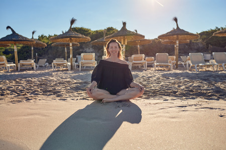 Smiling healthy barefoot woman sitting cross-legged on the beach as she prepares to meditate against a backdrop of resort beach umbrellas backlit by the evening sun casting her shadow across the sand