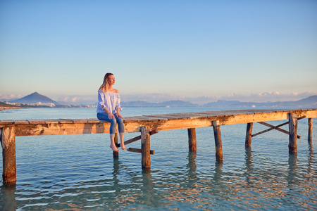 Barefoot woman sitting on a rustic wooden coastal pier or boardwalk at sunset with her legs dangling above the sea facing towards the setting sun