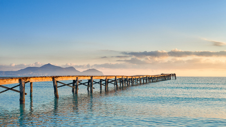Old wooden jetty or pier stretching out into the ocean at sunset lit by the warm glow of the sun on the horizon with distant mountains over the water