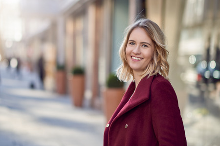 Attractive blond woman in warm maroon overcoat standing in a city street turning to look at the camera with a friendly smile Stock Photo