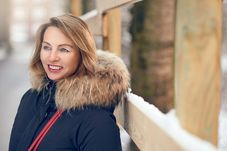 Attractive happy woman standing outdoors in winter wearing a fur trimmed jacket alongside a widow sill with fresh white snow in an urban street looking to the side with a smile and copy space Reklamní fotografie