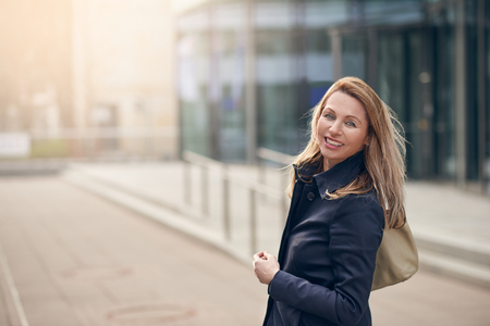 Happy smiling woman standing in the wind on an urban street with her long blond hair blowing around her face with lateral copy space