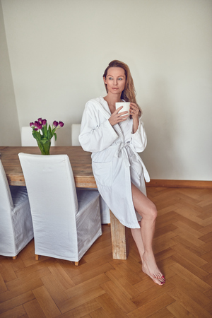 모닝 커피 앉아 즐기는 맨발로 목욕 가운에 매력적인 금발 여자가 집에서 식탁의 가장자리에 자리 잡고