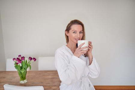 모닝 커피 앉아 즐기는 매력적인 금발 여자는 흰색 수건 목욕 가운에 신선한 봄 튤립 꽃병으로 나무 테이블의 가장자리에 자리 잡고