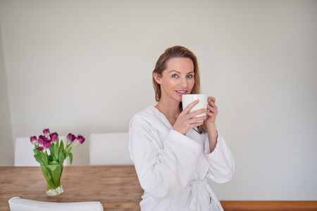 Attractive blond woman enjoying morning coffee sitting perched on the edge of a wooden table with vase of fresh spring tulips in a white towelling bathrobe smiling