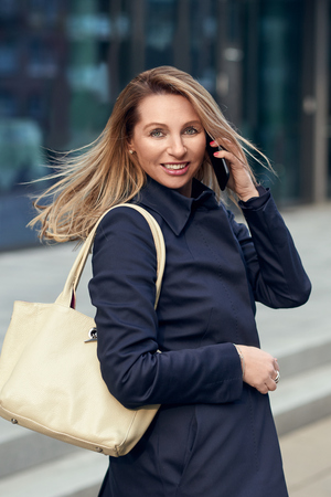 Attractive stylish blond woman talking on a mobile phone in an urban street turning to smile at the camera with her long hair blowing in the breeze Reklamní fotografie