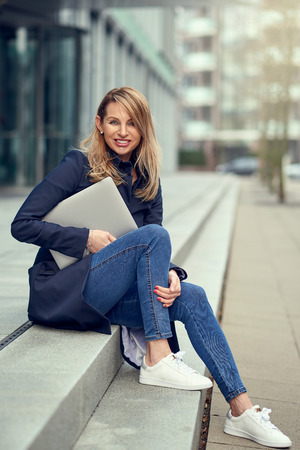 Trendy attractive blond woman in jeans sitting on exterior steps in town holding a laptop computer looking at the camera with a vivacious smile