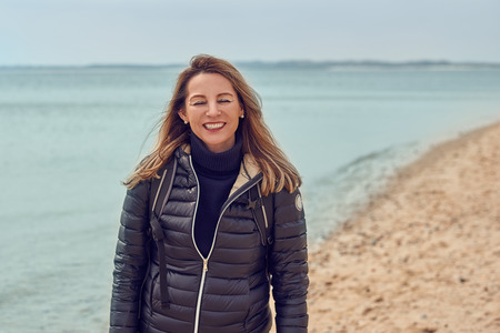 Attractive woman walking on a beach on a cloudy day wearing a backpack and jacket pausing at the edge of the sea to smile at the camera