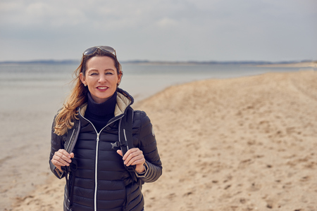 Attractive healthy woman enjoying a hike on the beach on a cold overcast day standing smiling at the camera on the sand holding the straps of her backpack