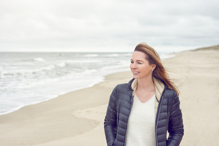Attractive trendy woman walking on a deserted sandy beach on a cloudy day at low tide turning to smile at the camera with copy space