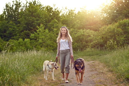 Happy young woman walking her dogs along a grassy rural track in spring looking at the camera
