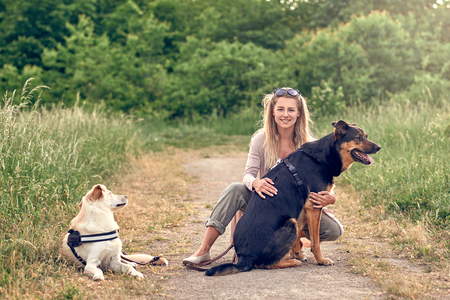 Happy blond woman with her two loyal dogs taking a rest on a rural farm road while exercising them kneeling down cuddling a large black and tan dog Foto de archivo - 103630281