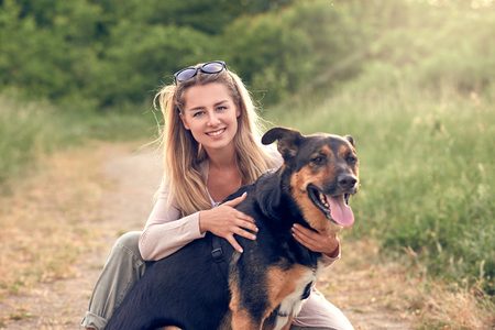 Happy smiling black dog wearing a walking harness sitting facing its pretty young woman owner who is caressing it with a loving smile outdoors in countryside