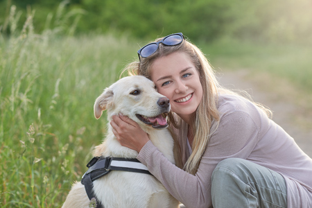 Happy smiling golden dog wearing a walking harness sitting facing its pretty young woman owner who is caressing it with a loving smile outdoors in countryside Stock Photo