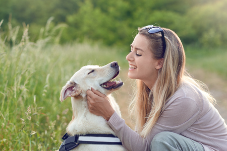 Happy smiling golden dog wearing a walking harness sitting facing its pretty young woman owner who is caressing it with a loving smile outdoors in countryside Archivio Fotografico - 103630286