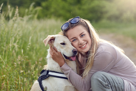 Happy smiling golden dog wearing a walking harness sitting facing its pretty young woman owner who is caressing it with a loving smile outdoors in countryside Stock fotó