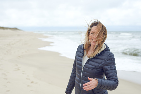 Smiling woman on a windy deserted beach laughing as the breeze blows her hair across her face, with copy space