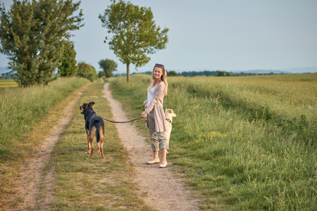 Attractive smiling blond woman with her two dogs on leads standing on a dirt road in farmland looking at the camera in evening light