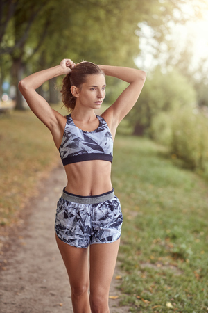 Slender fit shapely woman in sportswear walking along a shady tree lined path looking aside with her hands to her pony tail Фото со стока