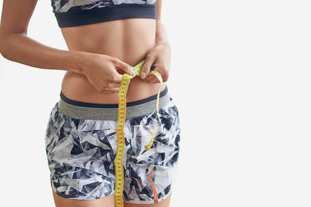 Slender woman wearing a trendy sports outfit measuring her waist with a tape measure in a close up cropped torso view in a weight loss and fitness concept over white Stock fotó