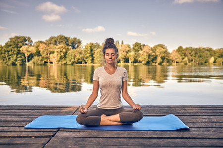 Smiling woman sitting on a yoga mat in the lotus position meditating on a wooden deck or jetty overlooking a tranquil lake in a healthy lifestyle concept Stock fotó